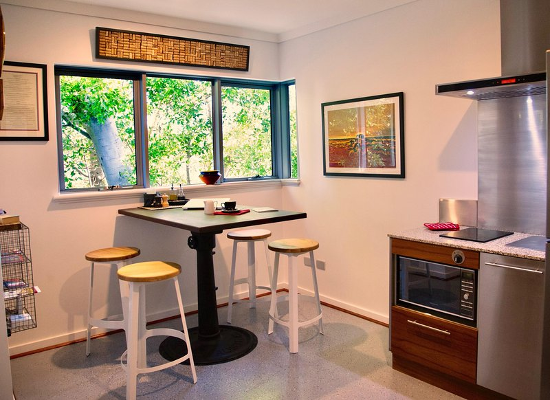 Enjoy the tree top view from the trendy and funky industrial kitchen