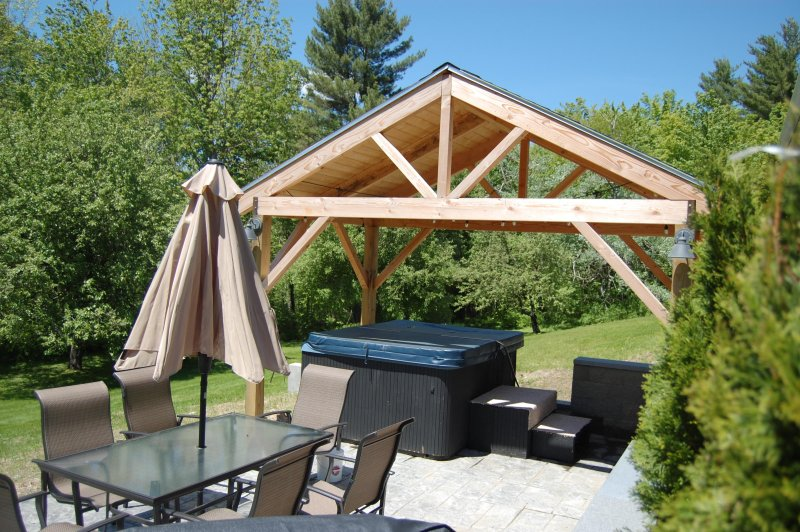 New patio with seating for 6, grill and covered Jacuzzi all overlooking large private  backyard