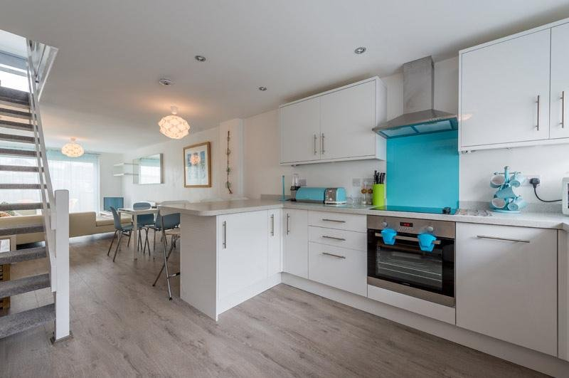 Salon ouvert / cuisine / salle à manger avec des portes-fenêtres donnant sur terrasse en bois, des sièges et une vue sur la plage de Porth.