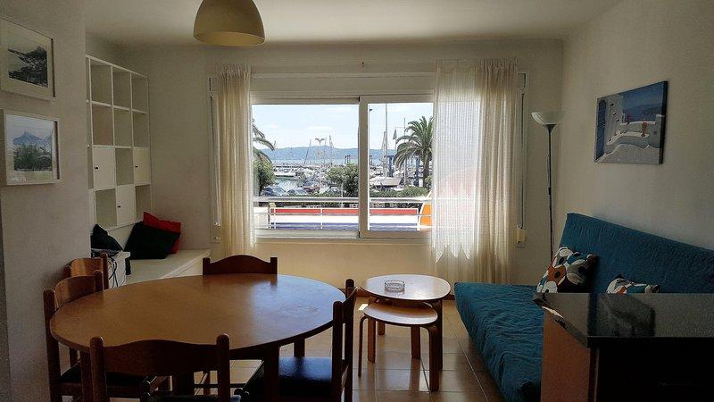 Living con gran ventana corredera, vistas al Passig Marítim y al Puerto Deportivo. Suelo  de Parquet