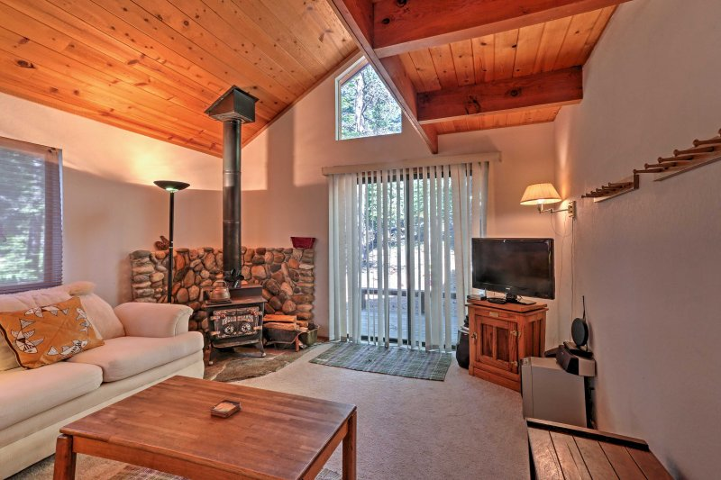 Wood paneling, a wood-burning stove, and comfortable furnishings create a warm and inviting ambiance at this 3-bedroom, 2.5-bathroom Truckee vacation rental cabin!