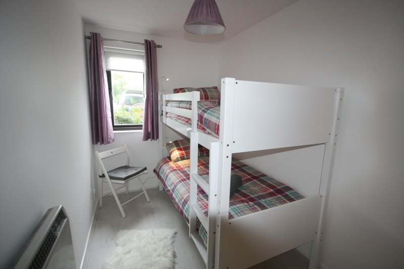 Kids bedroom with bunk beds, small chest of drawers, wardrobe and night lights