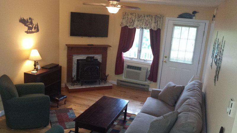 Spacious lounge room with flat screen TV, gas stove, and direct access to the balcony.