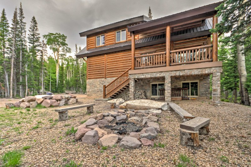 The cabin features a spacious yard with fire pit and outdoor seating areas.