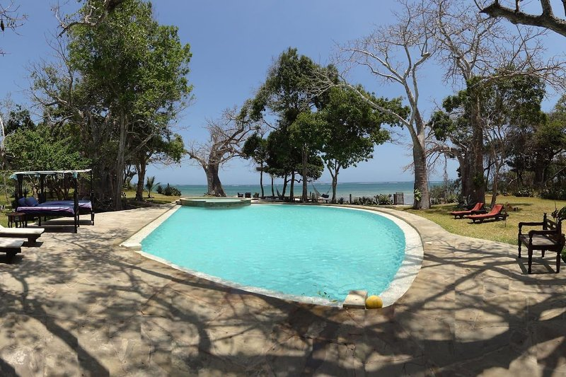 20 metres long swimming pool for adults and children facing secluded white sand beach ocean.