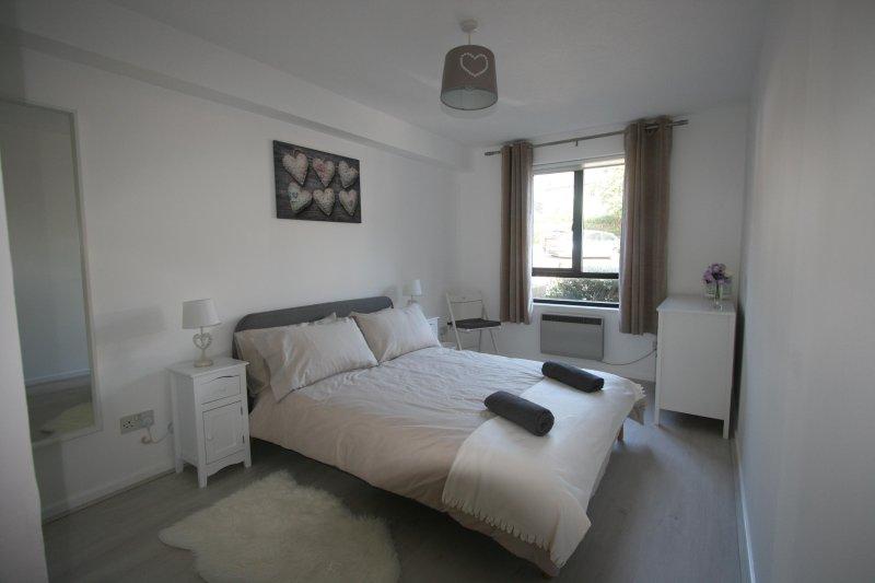 Modernes Master-Schlafzimmer mit Doppelbett, Nachttischen und Lampen, Kommode, Schrank und Spiegel