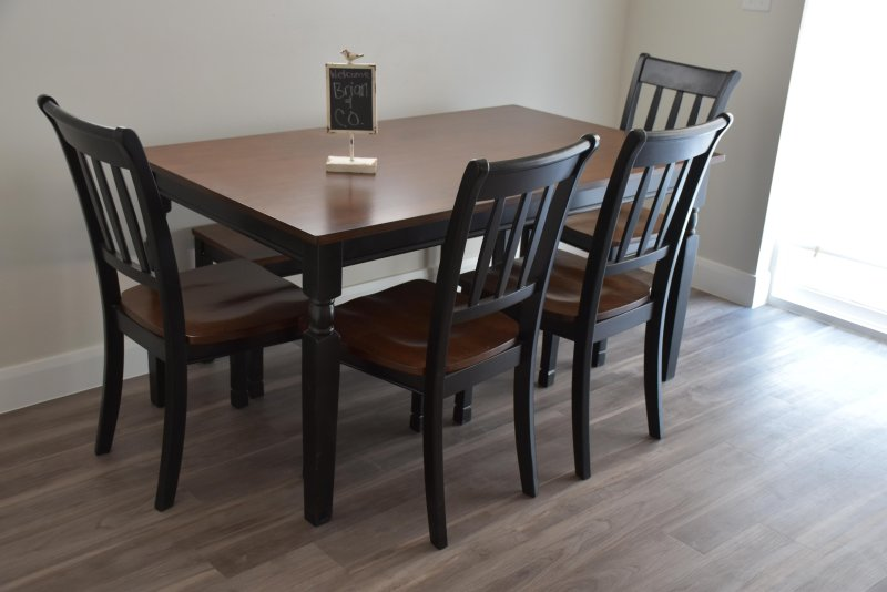 The kitchen table seats six with four on chairs and two on a bench