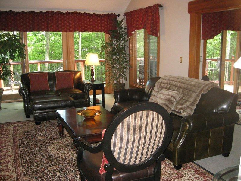 begane grond woonkamer met openslaande deuren naar een mooie dek.