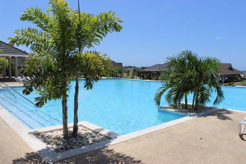Comunitaria turquesa Infinity Pool y Casa de la piscina con muchas tumbonas.