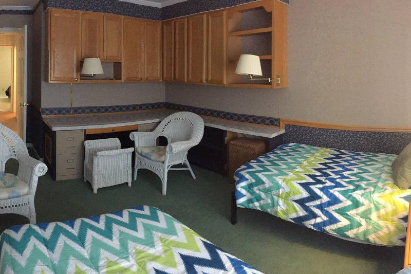 View of room with twin beds and sliding door to wrap-around deck