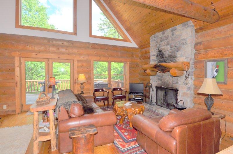 La sala de estar abierta con chimenea de leña y gran chalet de Windows
