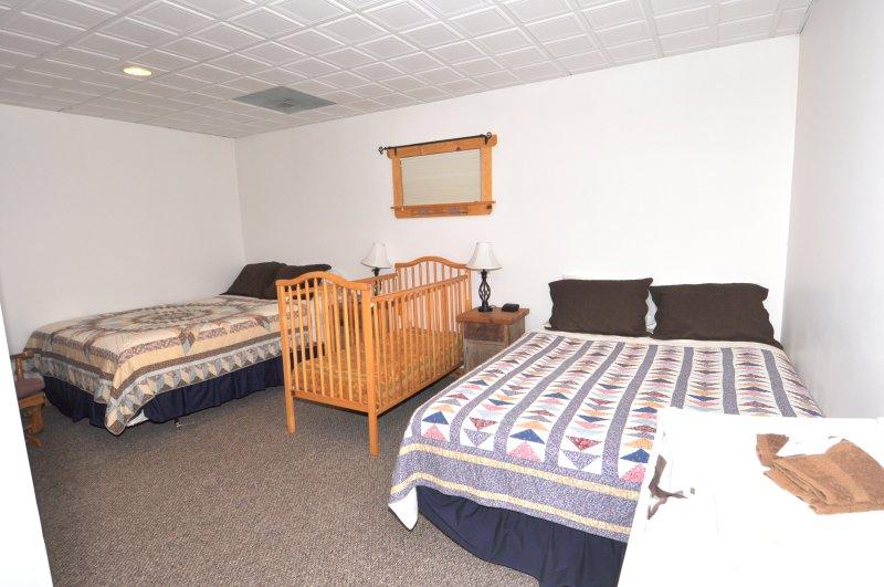 Dormitorio de nivel inferior situado junto a la Den con dos camas y cuna completa