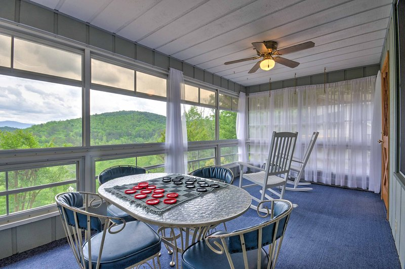 Floor-to-ceiling windows flood the sunroom with natural light.