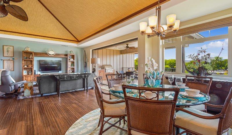 Table à manger élégante pour six personnes avec vue sur le salon et portes coulissantes à lanai supérieur au-delà.