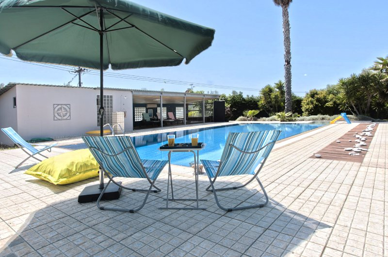 Outdoor swimming pool, relaxing area with chairs for sunbathing