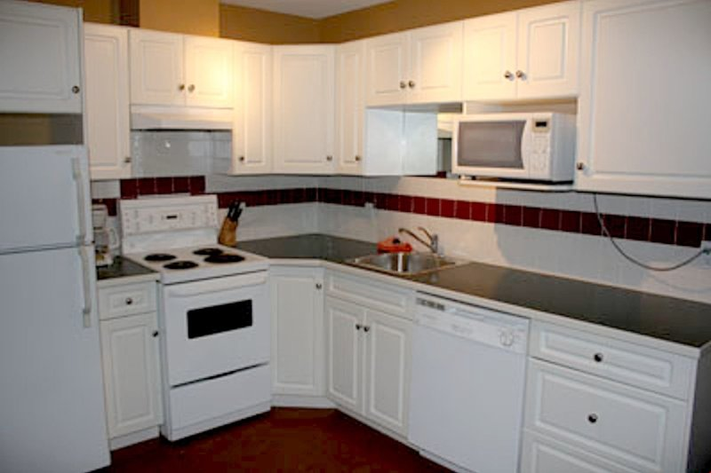 The kitchen features a stove, oven, microwave, dishwasher, fridge and coffee maker