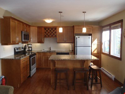 The fully-equipped kitchen features granite countertops and stainless steel appliances