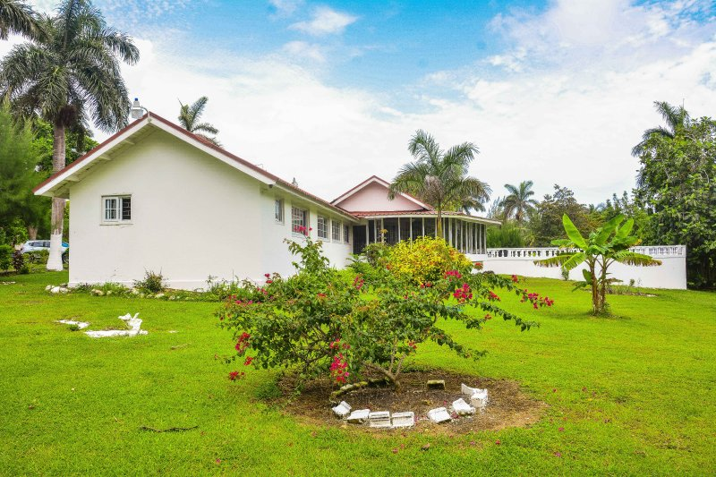 The exterior of villa Patiently Waiting set in fruited landscaped gardens minutes away from beach