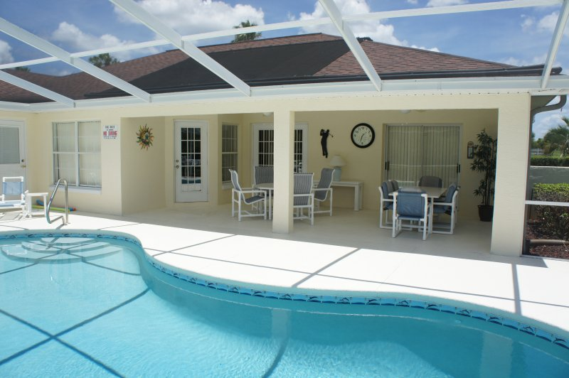 Pool with outdoor living area. Comfortable seats, dining table and ceiling fans