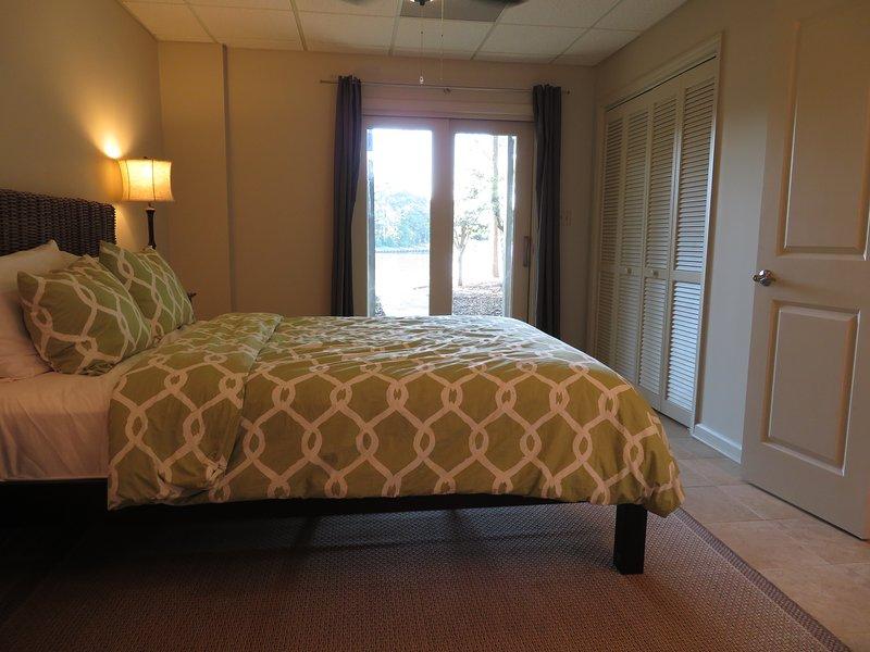 Lägre nivå sovrum med en dubbelsäng. Rummet delar ett bad med ett sovrum.