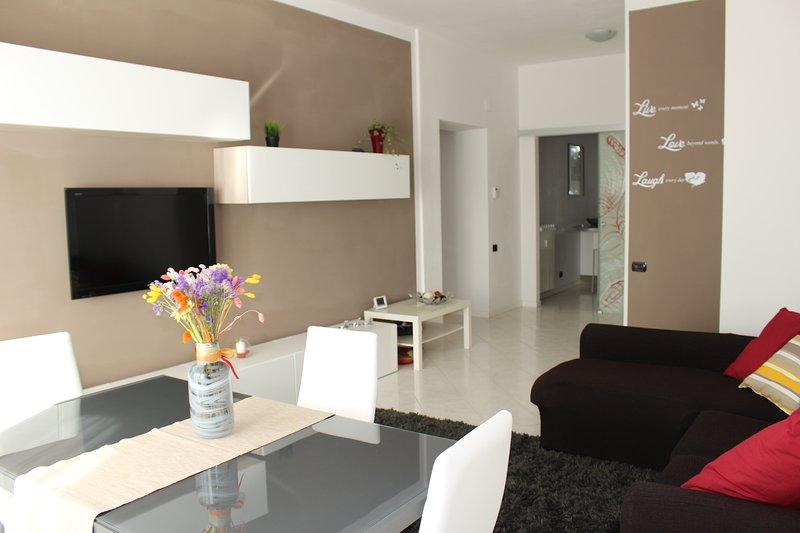 habitación con televisor de pantalla plana, sofá de 3 plazas y mesa de vida para pranzare.Accesso a la terraza