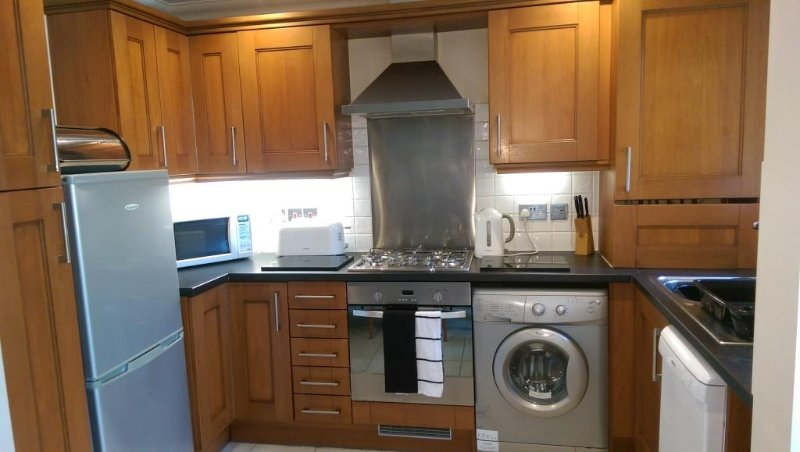 Kitchen with microwave, fridge/freezer, dishwasher, washing machine. Lots of pans, cutlery, crockery