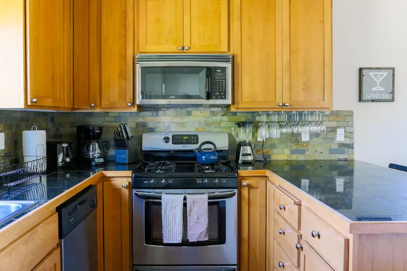 The modern kitchen is equipped with a gas stovetop and stainless steel appliances.  (Note: The Market is the newest addition to our portfolio; photos shown are of our identical rental next door.)