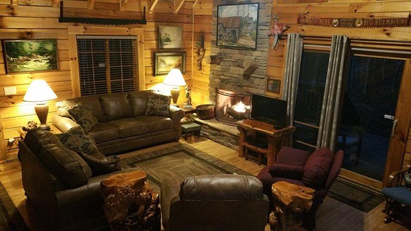 Disfrutar de un fuego acogedor en la gran sala a Big Rock Log Cabin.