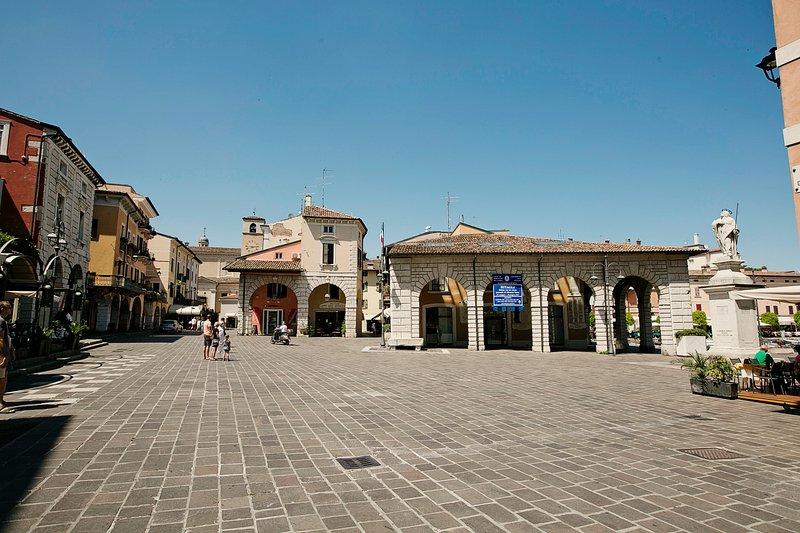 Piazza Malvezzi avec des magasins, des terrasses et des restaurants