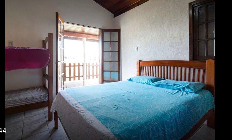Dormitorio con una cama doble y una litera con vistas al mar.