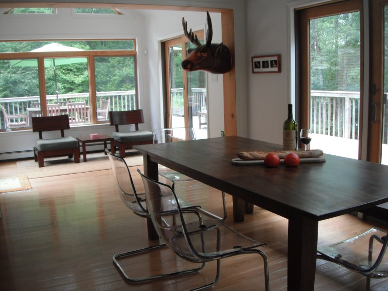 Dining room with 8ft. farmhouse table and windowed seating area.