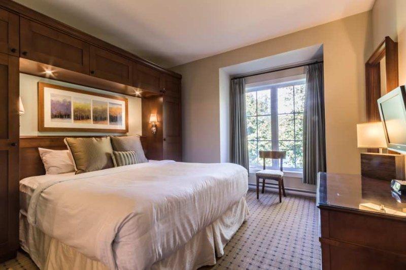 O quarto tem uma cama king size e TV de tela plana