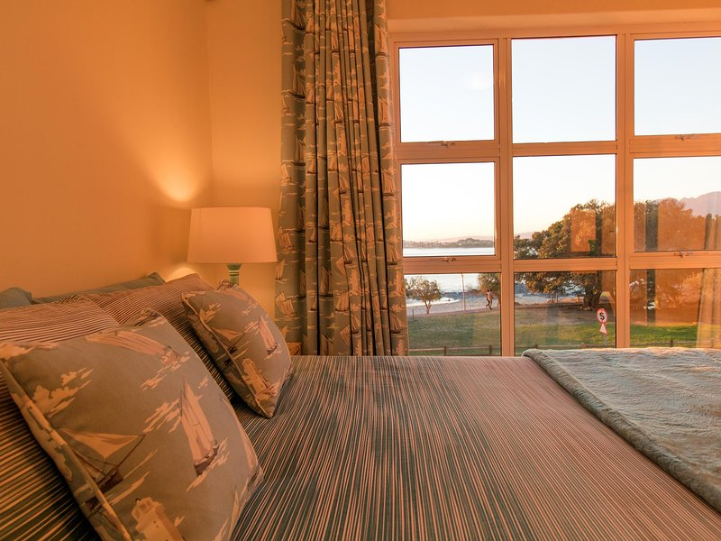 Enjoy the warm glow of morning sunshine from your bed with sea views