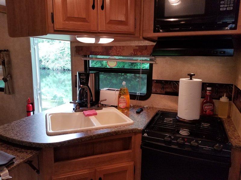 cozinha totalmente funcional, com um fogão, forno, microondas e uma geladeira cheia e freezer