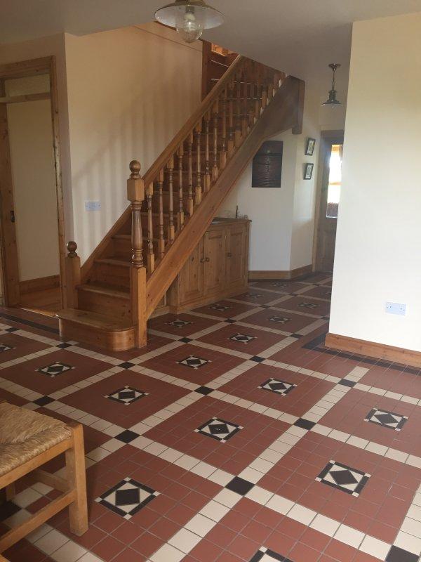 Hall de entrada que conduce a la planta alta; sala de estar con azulejos viejo mundo