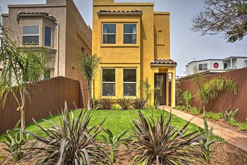 Esta casa de estuco ofrece plantas exuberantes, palmeras y césped.