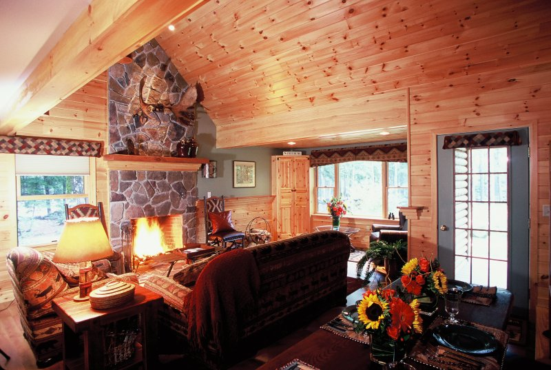 Beautiful wood paneling, a stone wood-burning fireplace, and stylish, rustic decor fill the interior of this 3-bedroom, 4-bathroom vacation rental house.