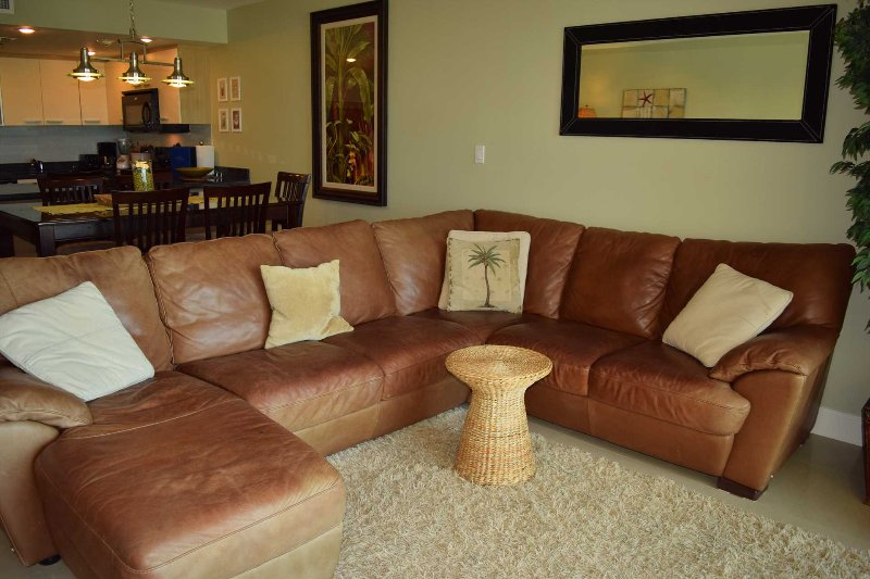 Living room with comfortable leather sofa set including a relaxing ottoman.