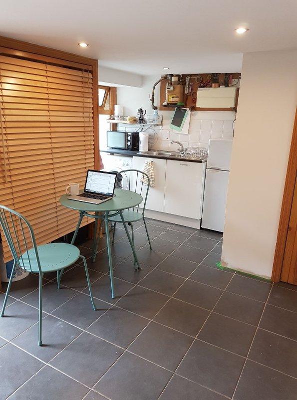 Pequeña área de cocina con nevera-congelador, lavadora y cama individual. Tetera, tostadora, microondas,
