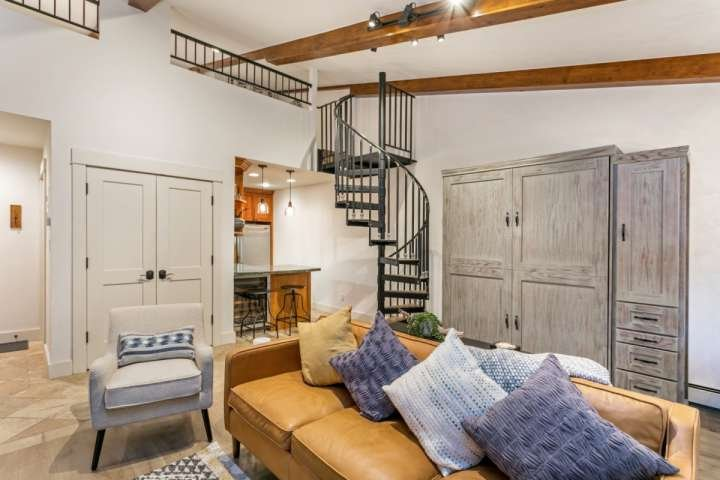 Queen size Murphy bed is located behind the sofa, spiral staircase (note the height & slope at the top) lead to the queen and twin beds.