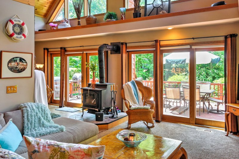 The magnificent living room features a cathedral ceiling, a wood-burning stove, a plush sectional sofa, a flat-screen satellite TV, and a wall of windows that allows natural light to fill the room.