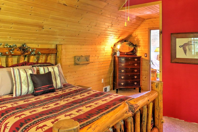 The second bedroom has a wonderful cabin feel with shiplap walls, a queen-sized bed, a full-sized bed, and a flat-screen satellite TV.