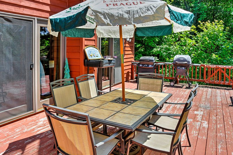 The gigantic wrap-around deck features to outdoor tables with chairs and umbrellas and a gas grill for all of your barbecuing needs.