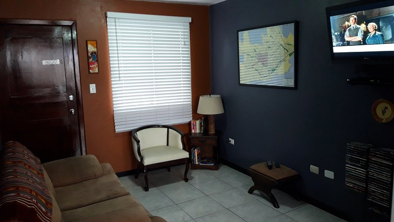 Living room with sofa, chair, flat screen TV, DVR, Stereo, and large map of Cuenca.