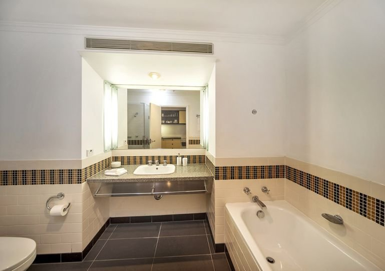 Full bathroom with a bath and shower, laundry is just done the hallway.