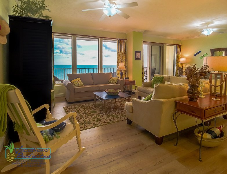 Large windows in the living room where you can clearly see the gulf over the balcony, tile and wood laminate floors throughout, with a wide variety of seating options for the whole family