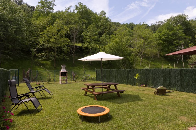 Large enclosed garden with barbecue and picnic table.