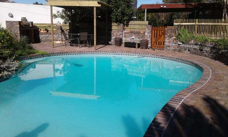 Pergola with seating in the pool area. Barbecue to the left of the picture.