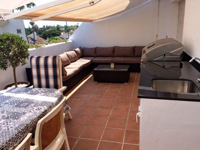 Dakterras met loungebank, barbecue, koelkast, tik en tafel voor 8