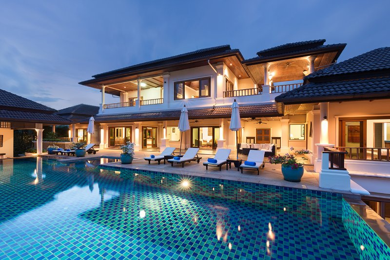 Swimming pool and villa at sunset